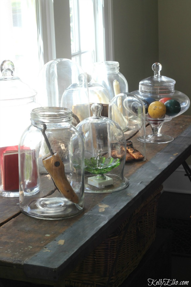 Love this table of curiosities - glass cloches and jars filled with unique finds kellyelko.com