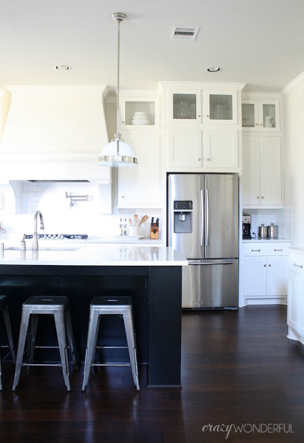 Love this white kitchen with black island and metal stools kellyelko.com