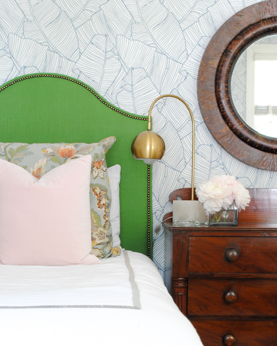 DIY green upholstered headboard and graphic leaf wallpaper