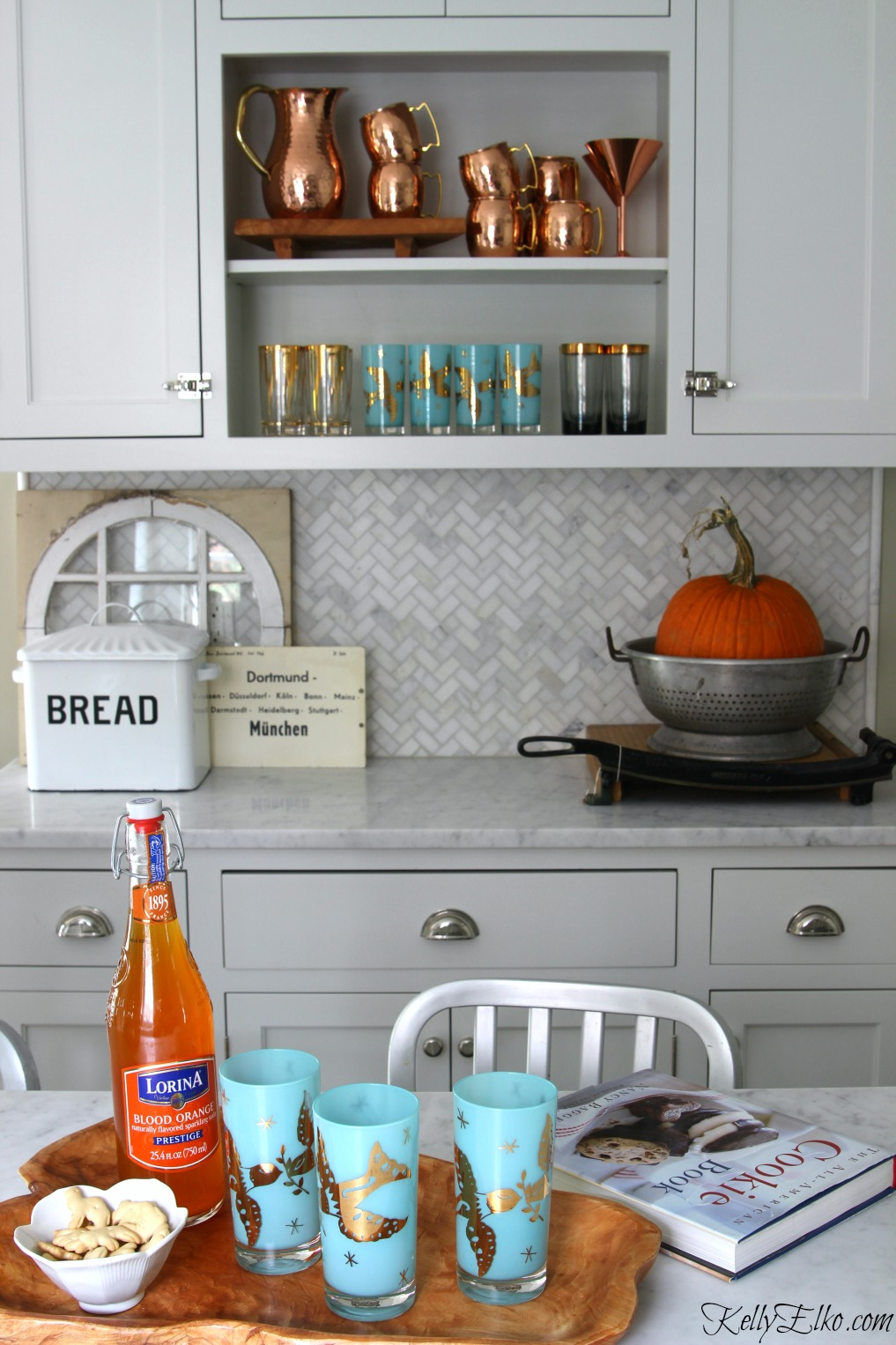 Love the open kitchen shelves with copper mugs and vintage drinking glasses on display kellyelko.com