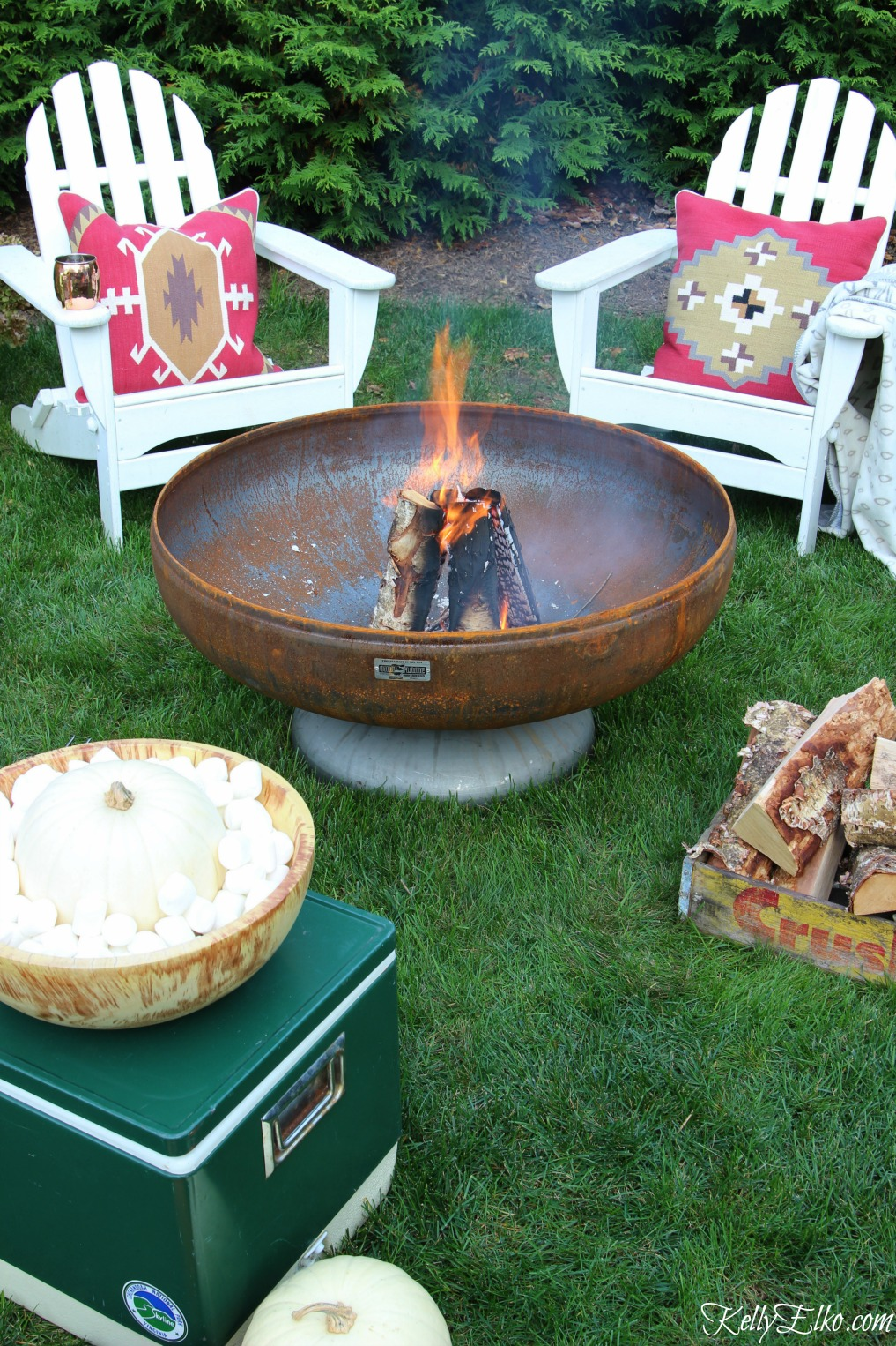Cozy fall fire pit - I love the red boho pillows and vintage finds like the old cooler and soda crate holding kindling kellyelko.com
