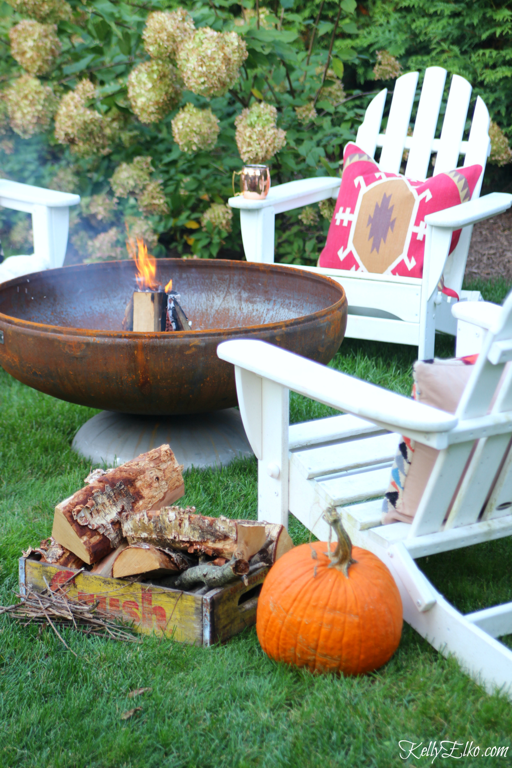 Love the patina on this fire pit surrounded by adirondack chairs and cozy throw and pillows kellyelko.com