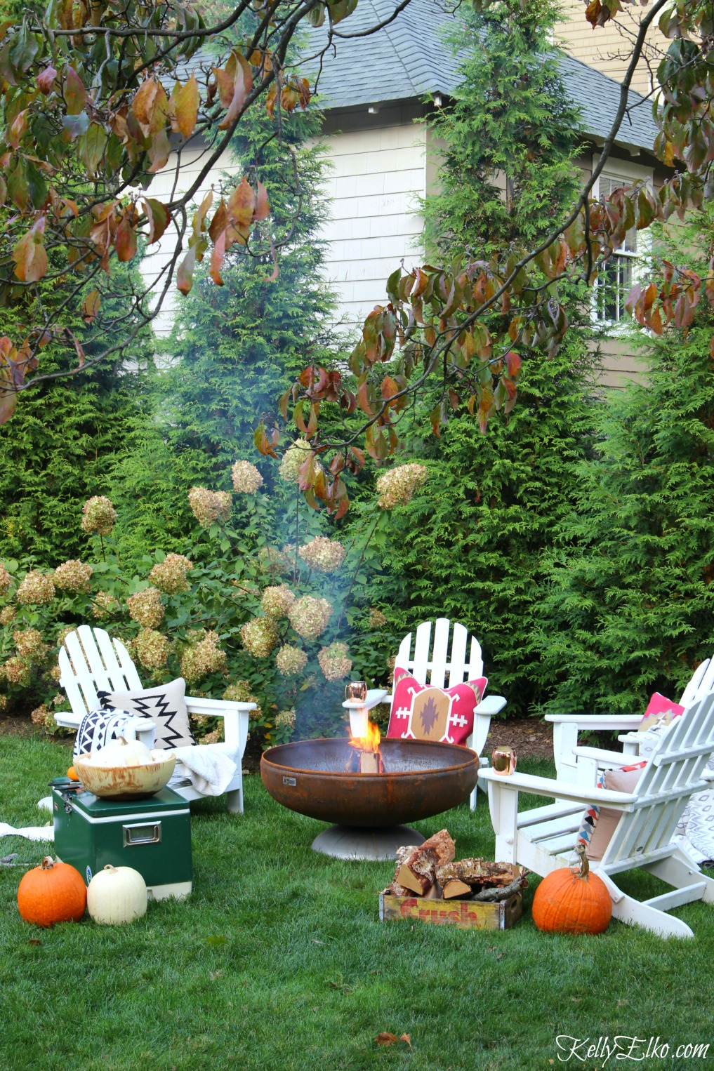 Love this fire pit surrounded by adirondack chairs piled high with boho throws and pillows kellyelko.com