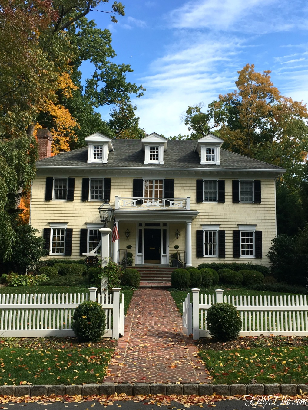 Charming colonial house with white picket fence - see more fall homes with curb appeal kellyelko.com