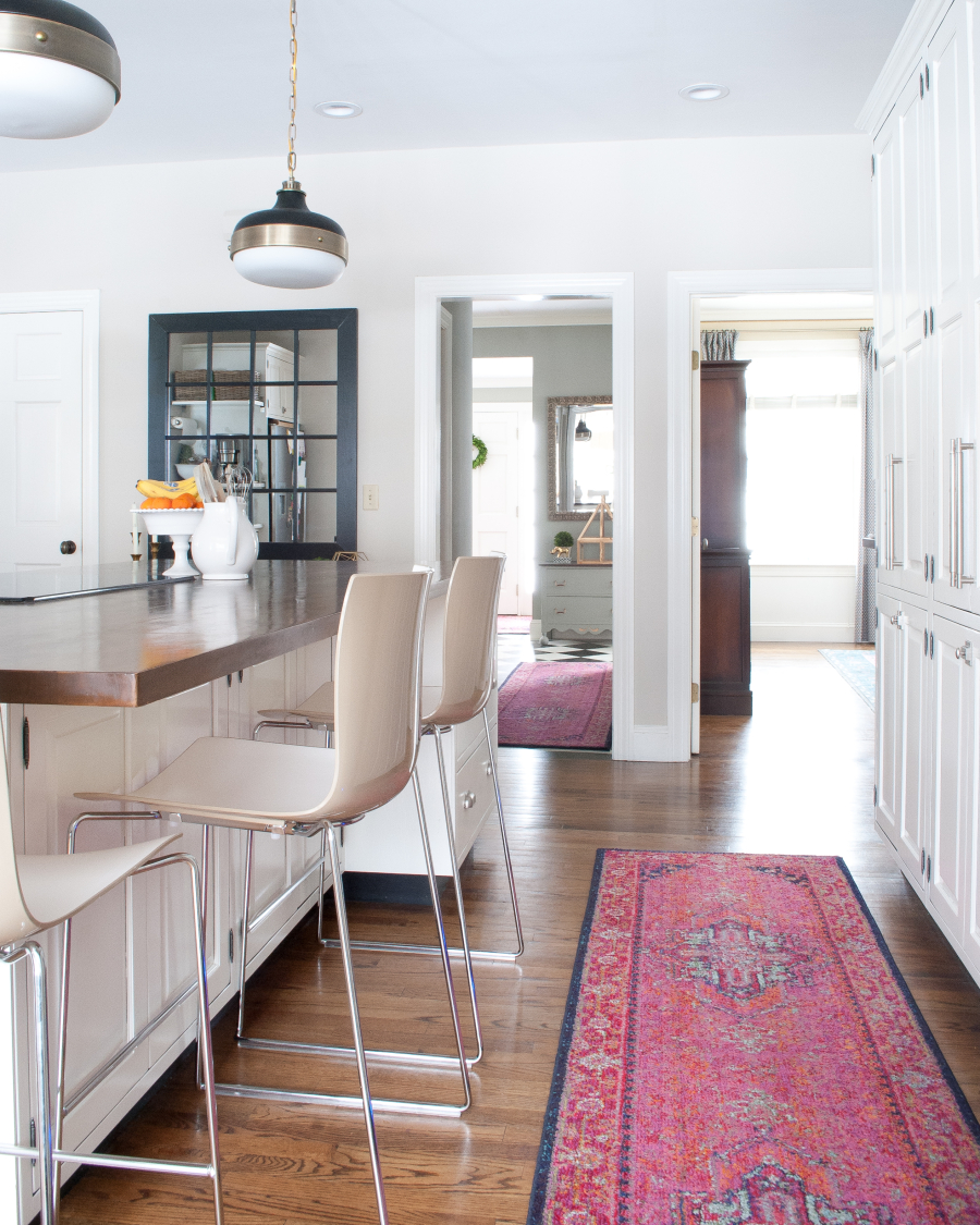 Love the pink Oriental rug in this white kitchen