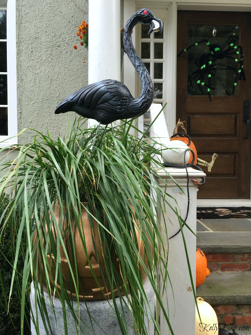 Love this Halloween porch with plastic pumpkin planter and zombie flamingos kellyelko.com