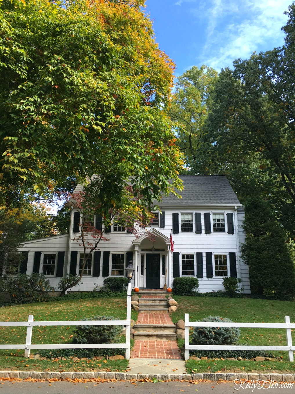 Love this classic white colonial house behind a picket fence - see more fall homes with curb appeal kellyelko.com