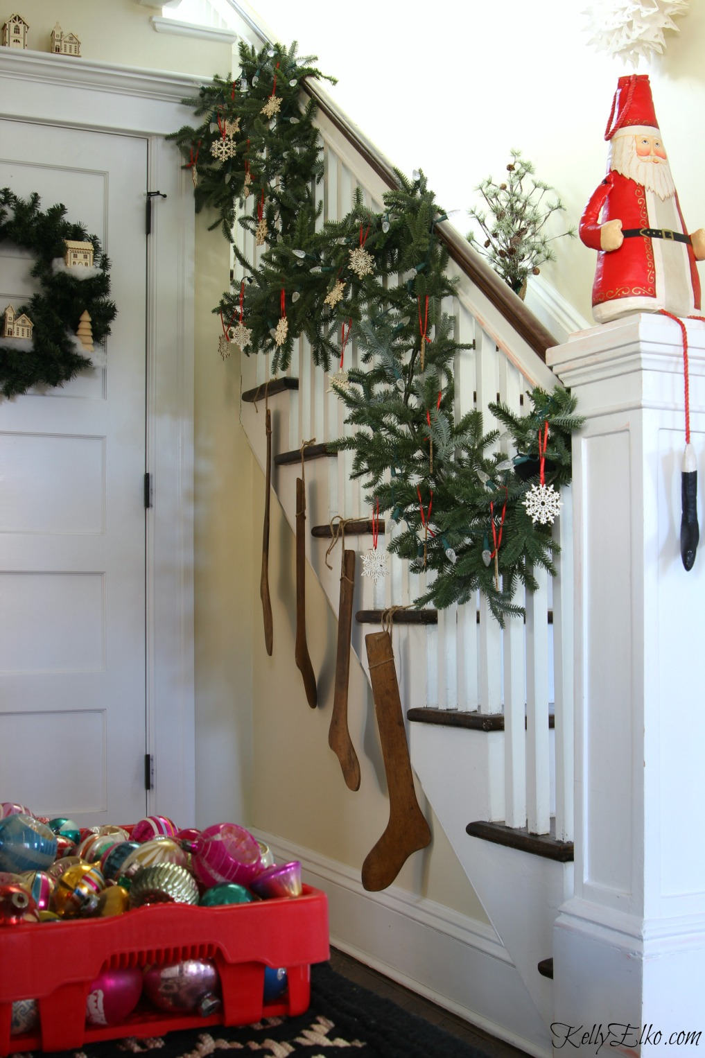 Love this lush Christmas garland on the staircase with wood snowflake ornaments kellyelko.com
