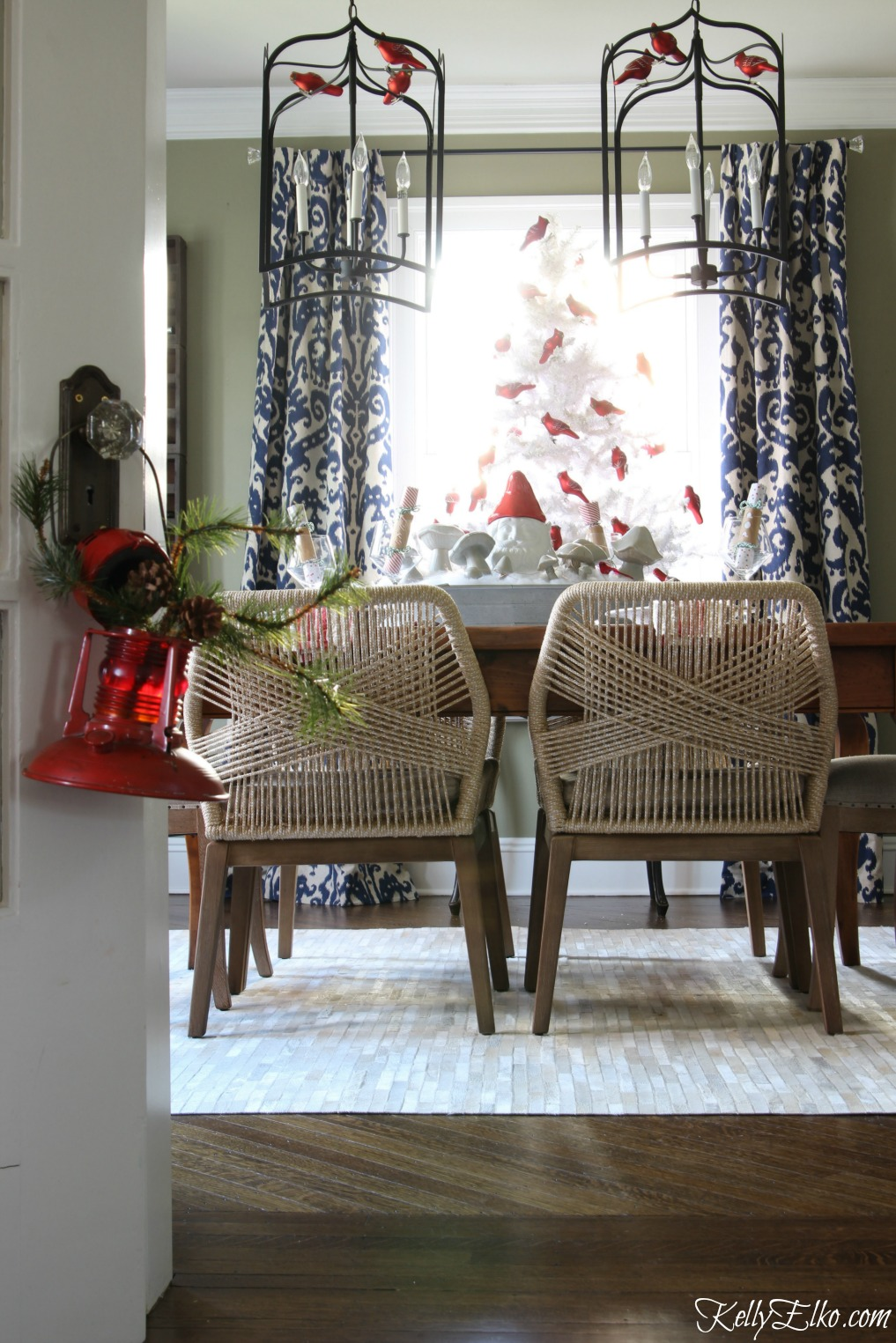 Love this festive Christmas dining room with white flocked tree and those amazing rope chairs! kellyelko.com