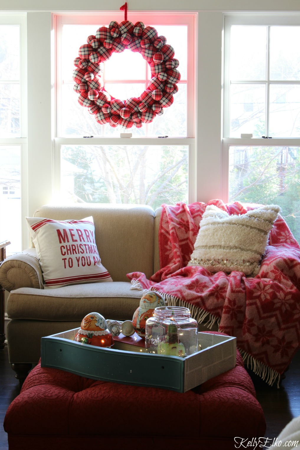 Cozy Christmas family room - love the huge plaid wreath and red snowflake throw blanket kellyelko.com