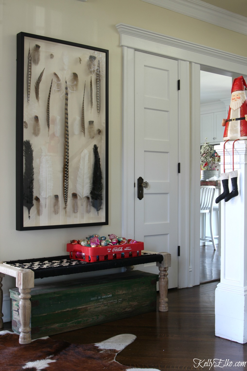 This foyer gets a festive Christmas makeover with a old soda crate filled with vintage shiny brite ornaments kellyelko.com