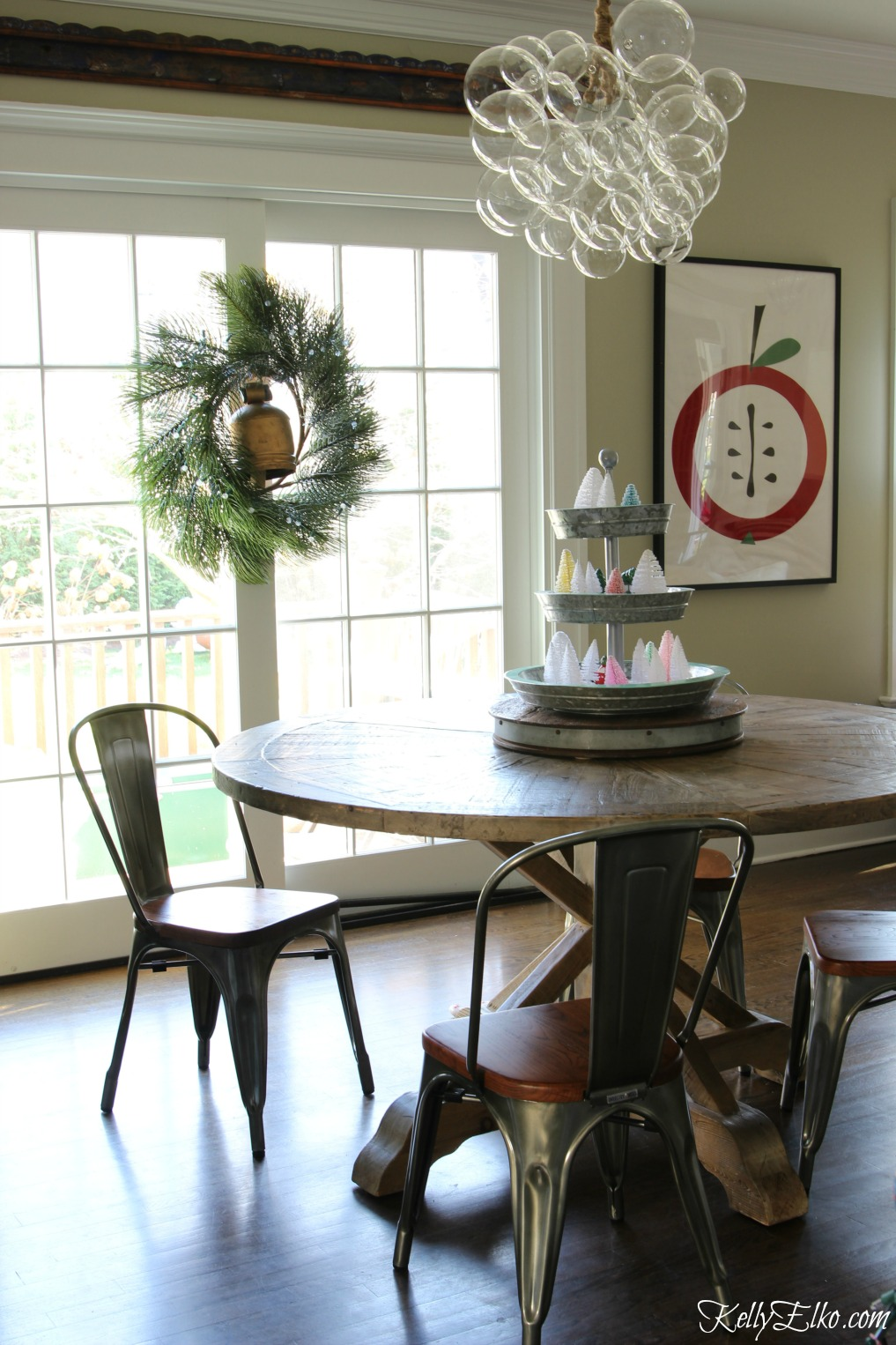 Love the wreath with brass bell in this festive Christmas kitchen ... and that bubble chandelier is amazing! kellyelko.com