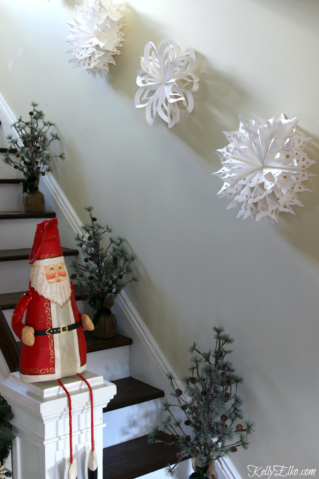 Giant paper snowflakes look amazing on the staircase wall kellyelko.com