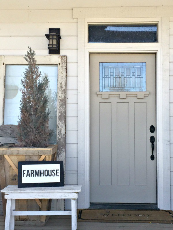 Love this gray front door on this charming farmhouse