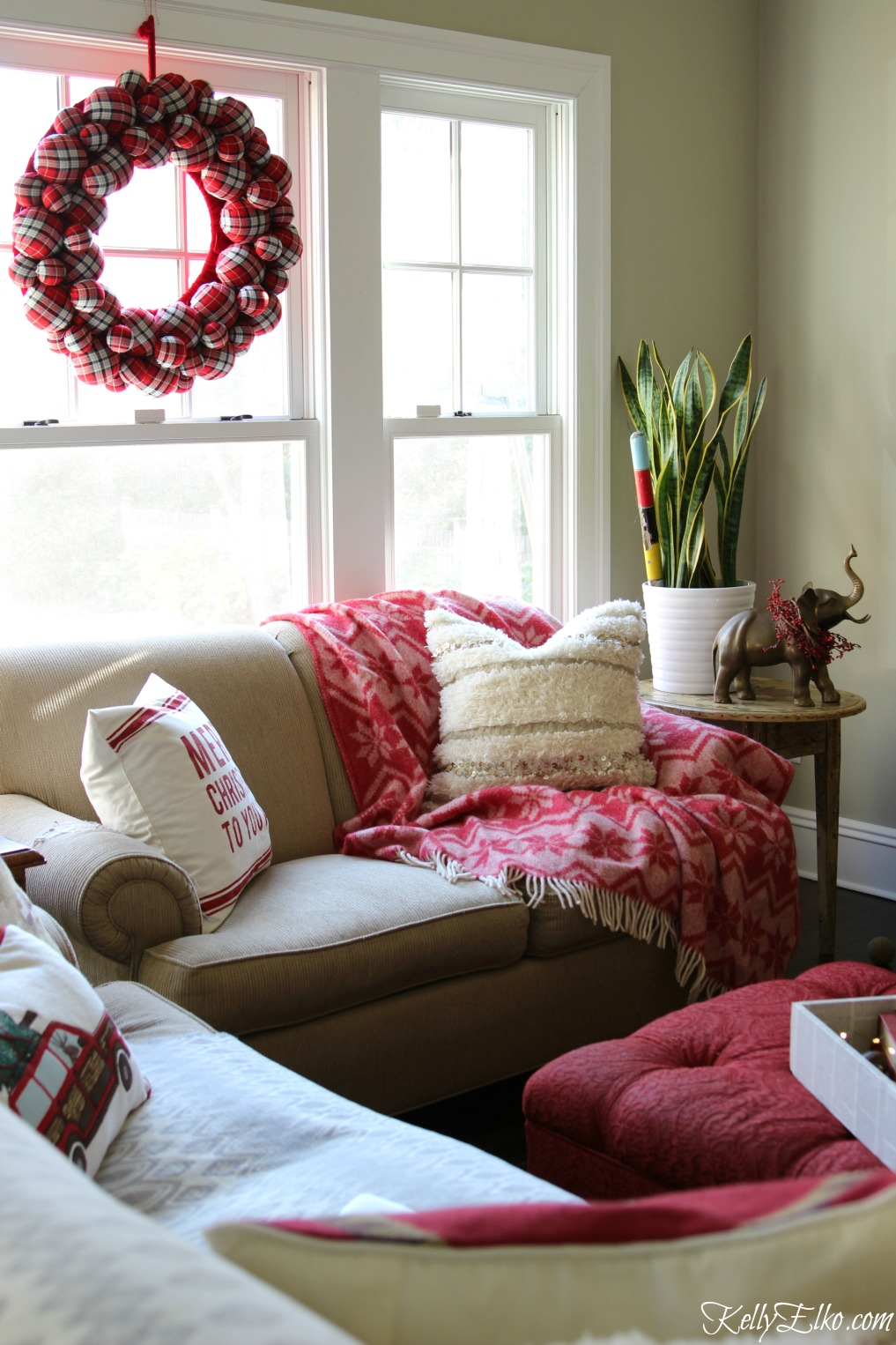 Love this festive red Christmas family room and the giant plaid wreath kellyelko.com