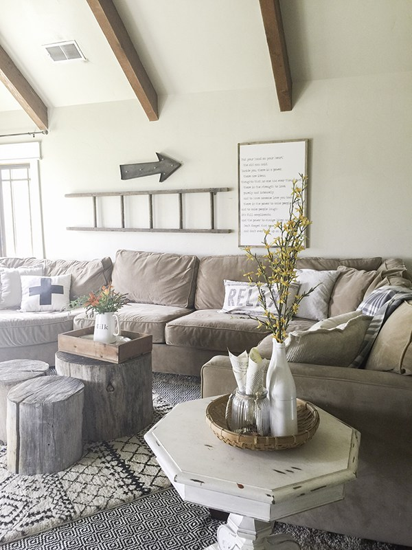 Cozy family room with sectional sofa, layered rugs and log slice coffee table