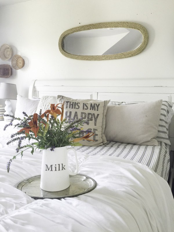 White master bedroom with striped bedding