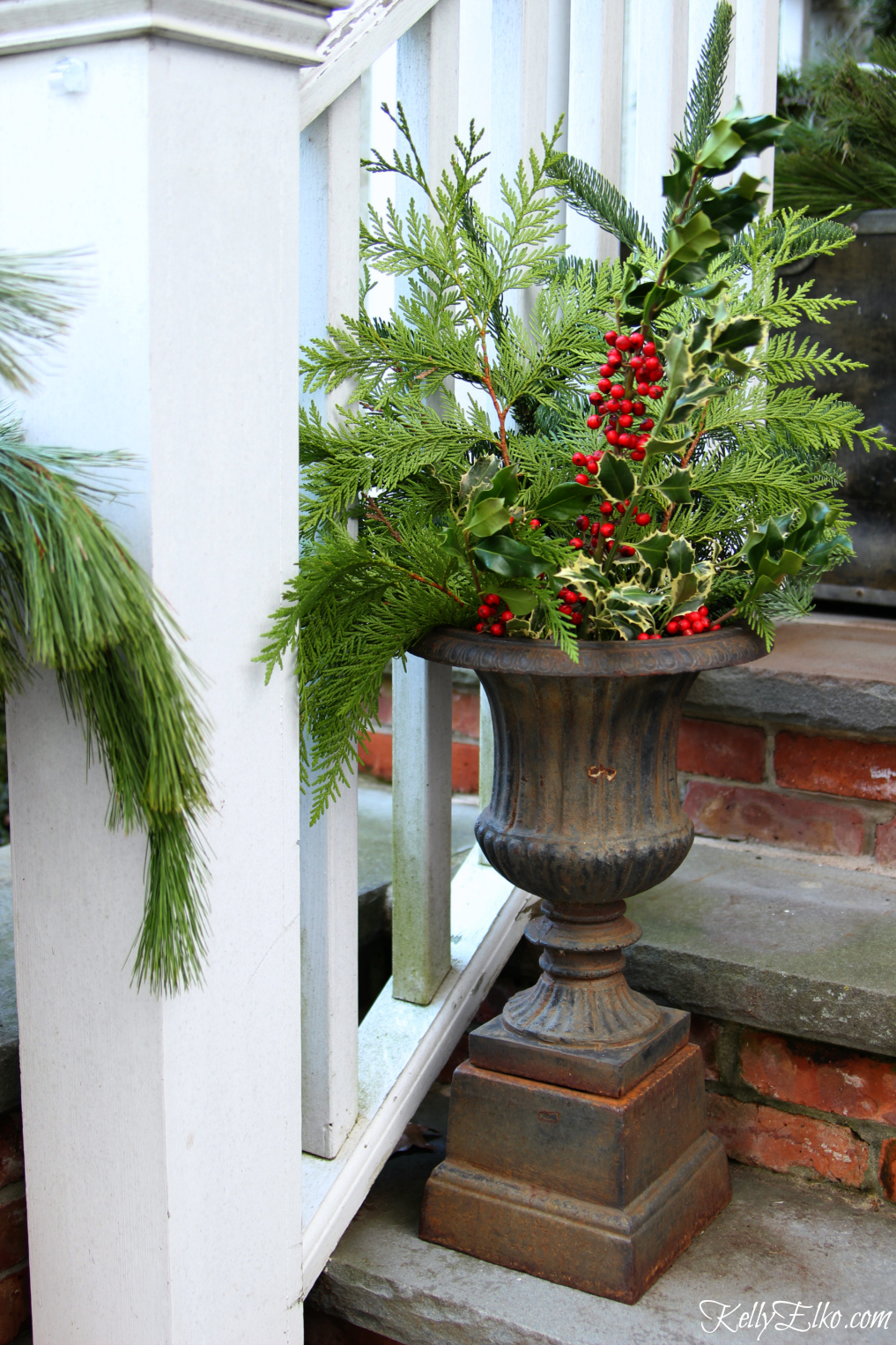 Christmas porch with fresh greens in an antique urn kellyelko.com