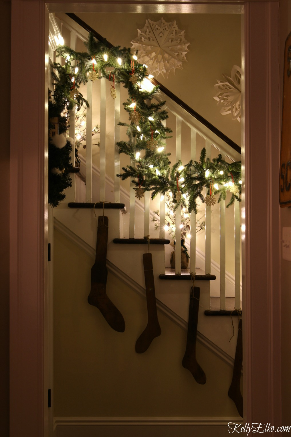Christmas Lights at Night Home Tours - 35 homes by the glow of light - love this gorgeous banister with garland and stocking stretchers kellyelko.com