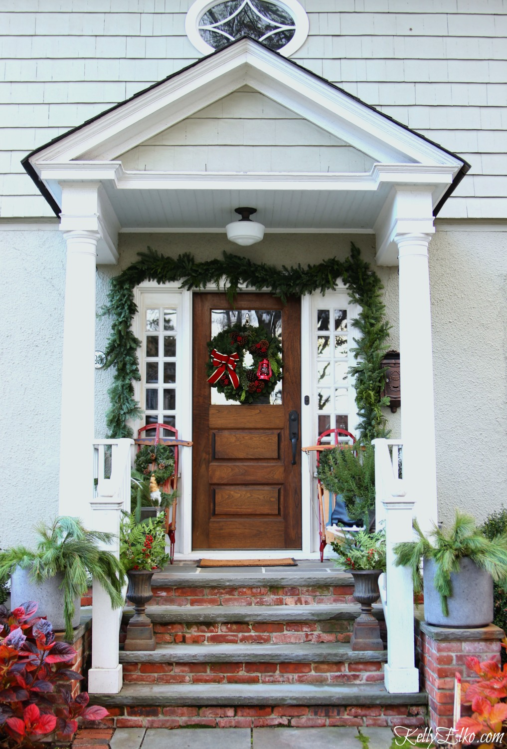 Beautiful Christmas porch with vintage sleds and lush fresh greens kellyelko.com
