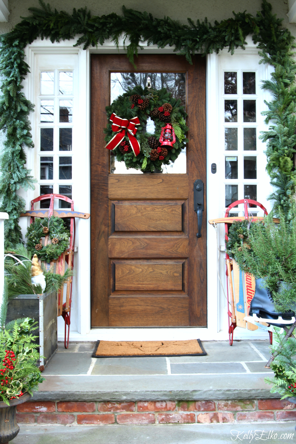 Vintage Christmas Porch Decorating Ideas - love the pair of old sleds kellyelko.com #christmas #christmasporch #christmasdecor #vintagechristmas #sled #christmasdoor #christmaswreath #christmasgarland #kellyelko