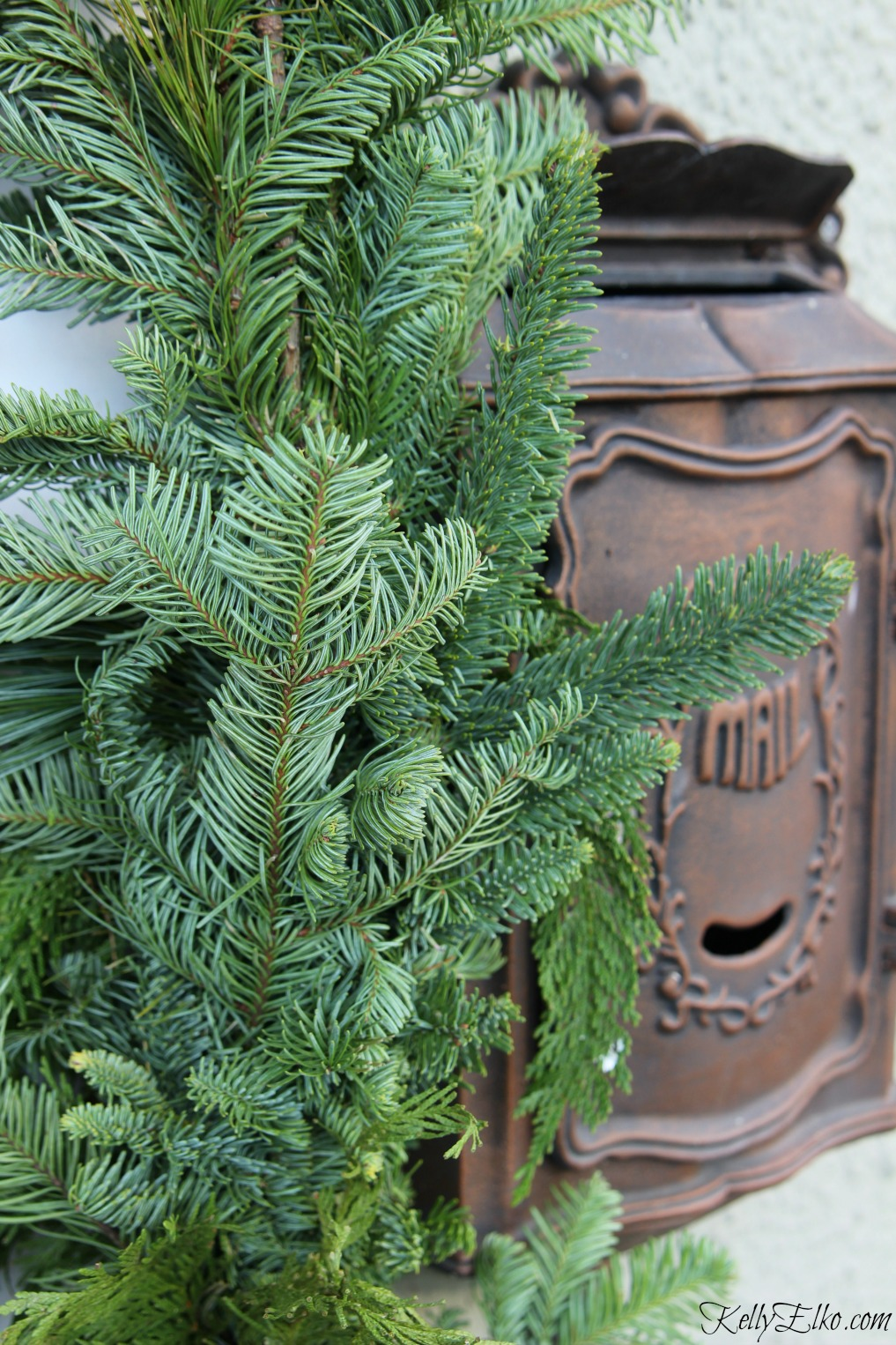 Thick and lush garland surrounds the front door of this beautiful Christmas porch kellyelko.com