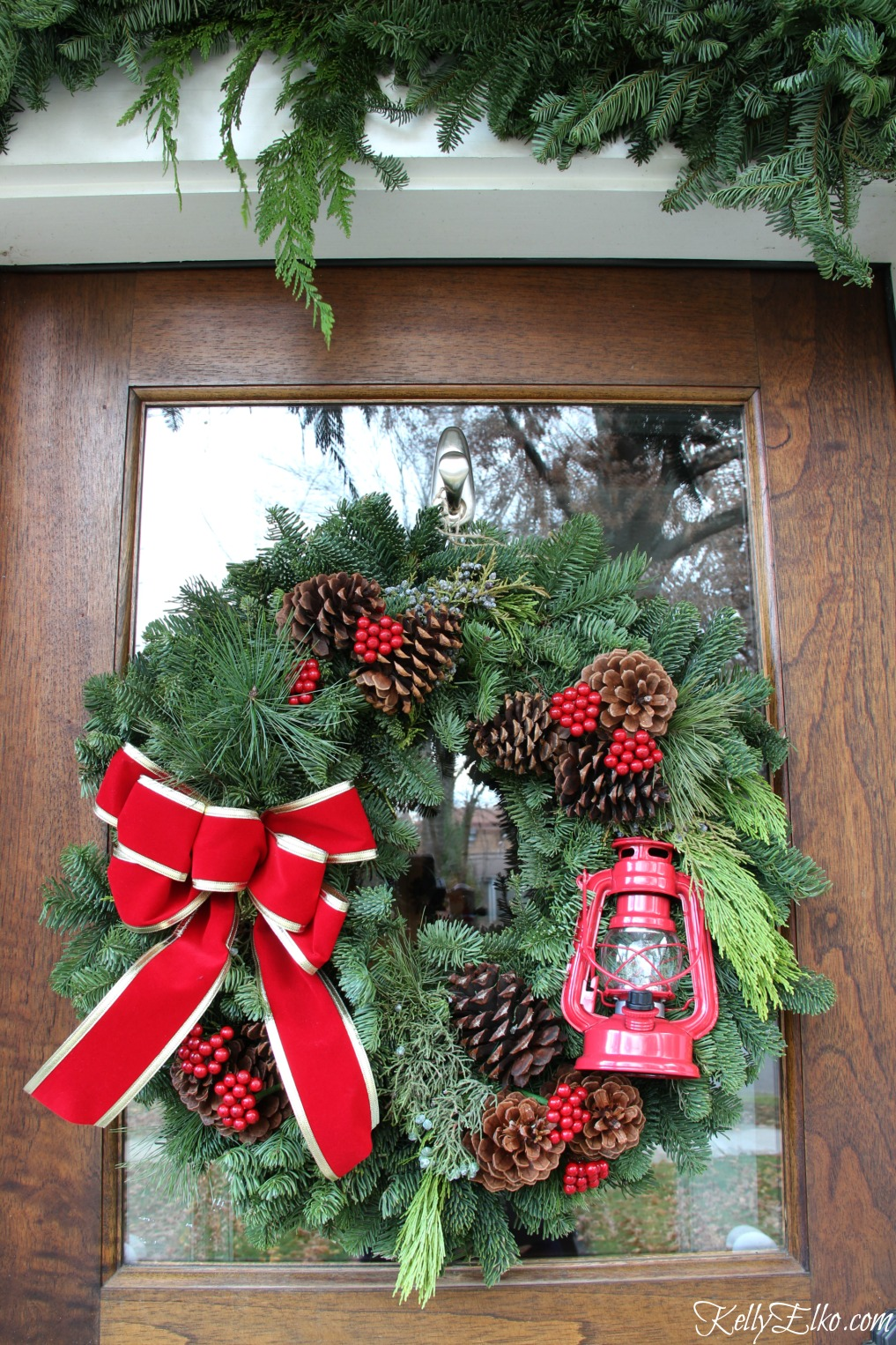 Red lantern Christmas wreath on this beautiful front door kellyelko.com