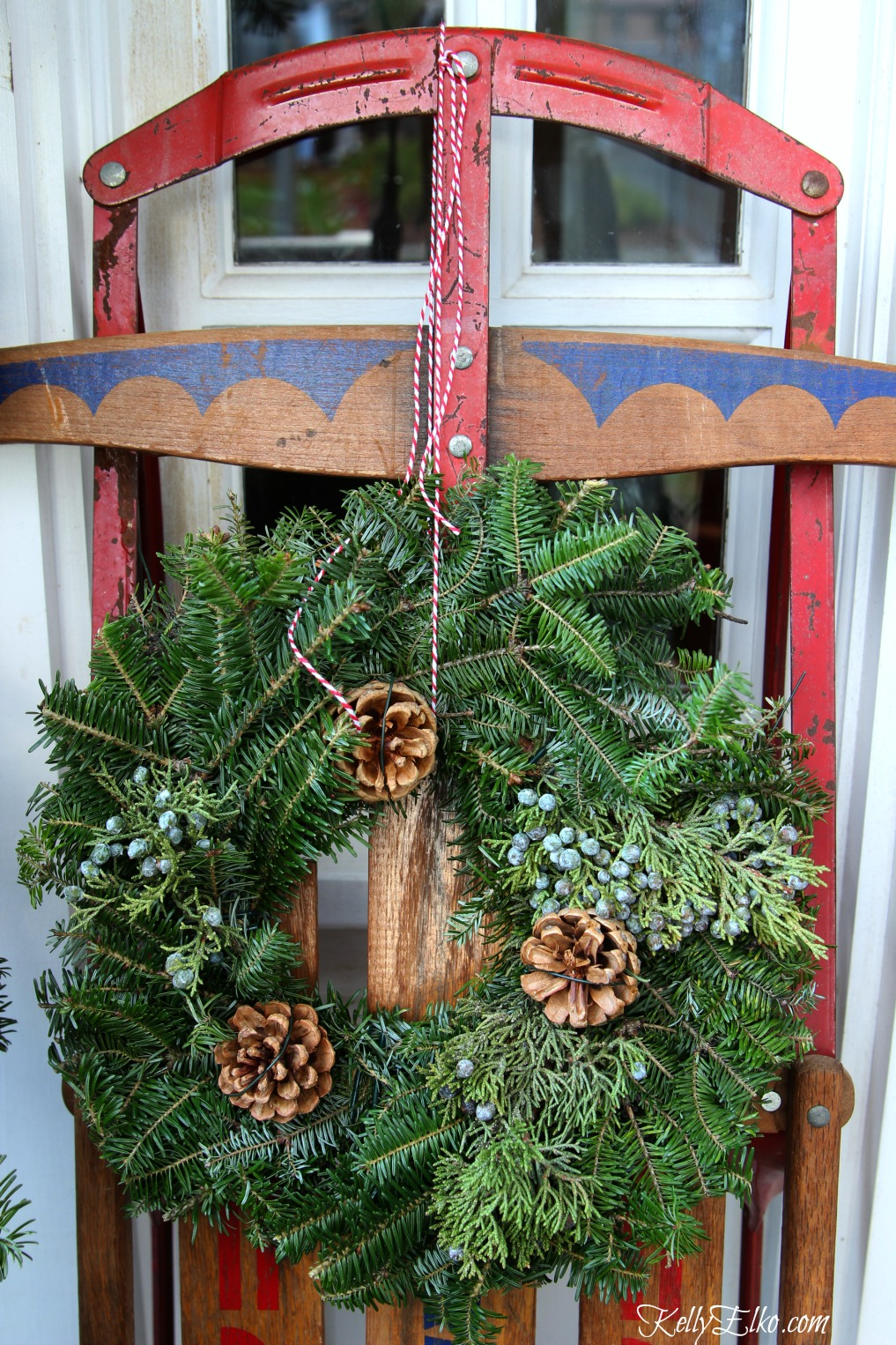 Vintage sled with wreath on this welcoming front porch kellyelko.com
