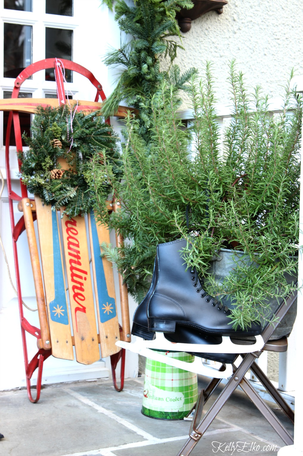 Christmas porch with vintage finds like the old sled, ice skates, metal chair and plaid cooler kellyelko.com #christmasporch #outdoorchristmasdecor #vintagechristmas #sled #kellyelko