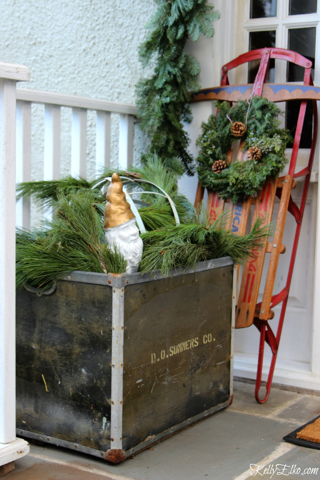 Vintage Christmas porch decorating ideas - love using a big metal container to hold sprigs of fresh greenery kellyelko.com #christmasporch #christmasdecor #outdoorchristmasdecor #vintagechristmas #sled #kellyelko #christmaswreath