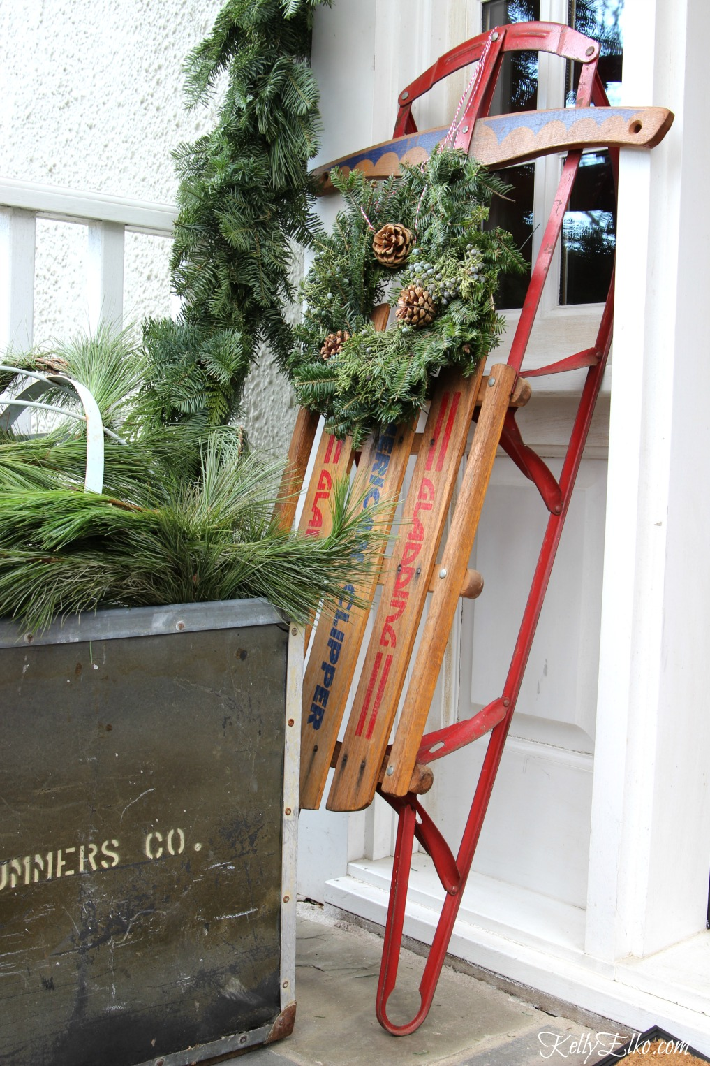 Vintage wood sled with wreath on this welcoming Christmas porch kellyelko.com