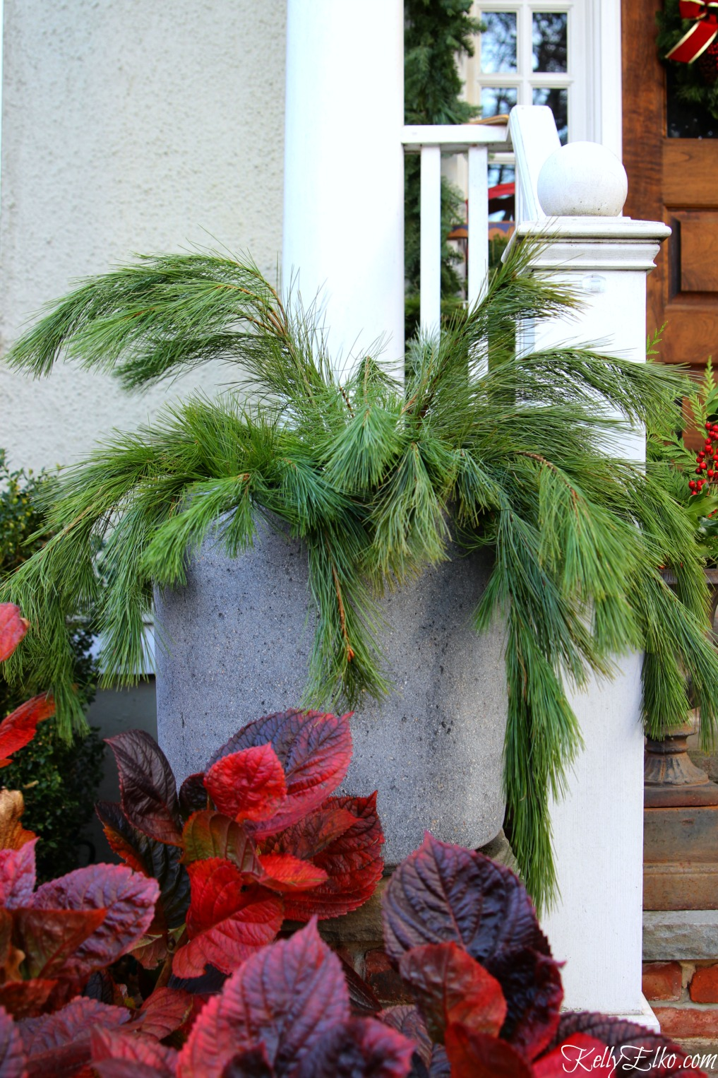 Love this Christmas front porch with planters filled with fresh greens kellyelko.com