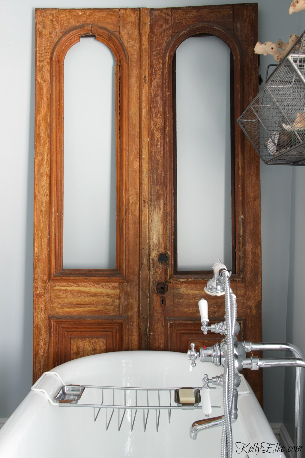 Add antique pieces to a bathroom to add warmth - love these antique arched doors kellyelko.com