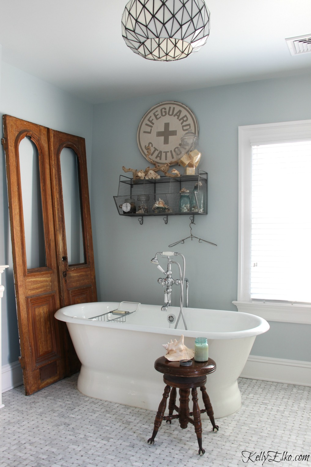 Love this master bathroom with free standing tub and marble tile - the antique doors add warmth and character kellyelko.com