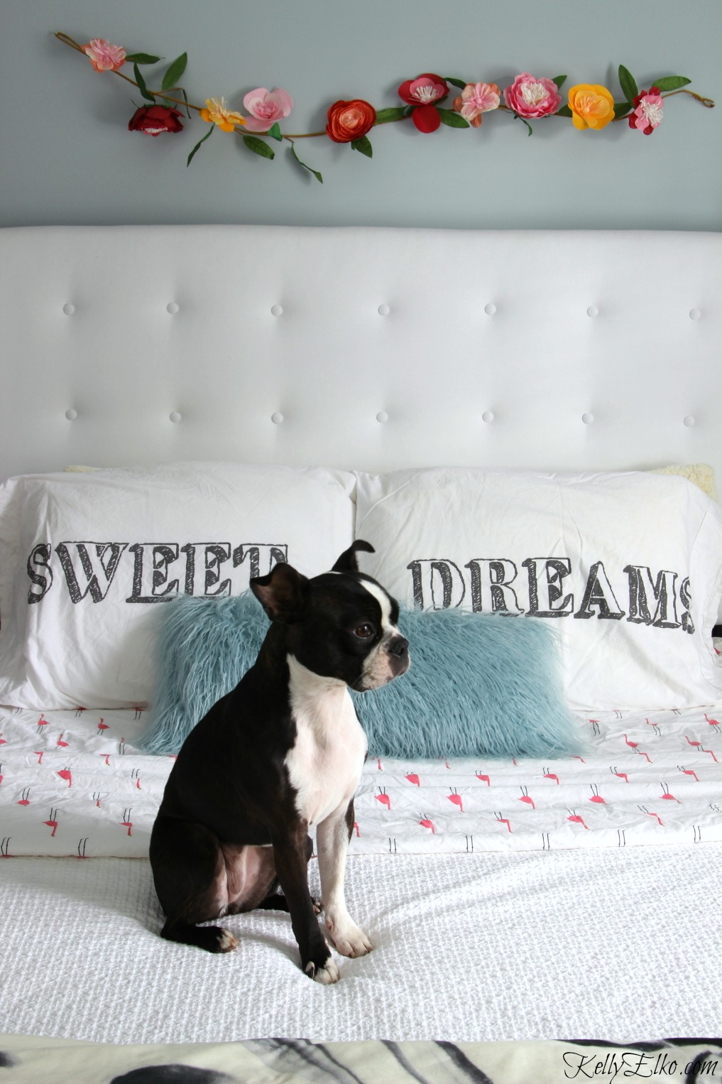 White tufted headboard gives this blue bedroom a glam look and I love the paper flower garland kellyelko.com