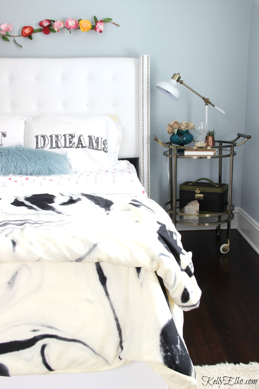 Glam bedroom makeover - love the blue paint, white tufted bed and bar cart as a nightstand kellyelko.com