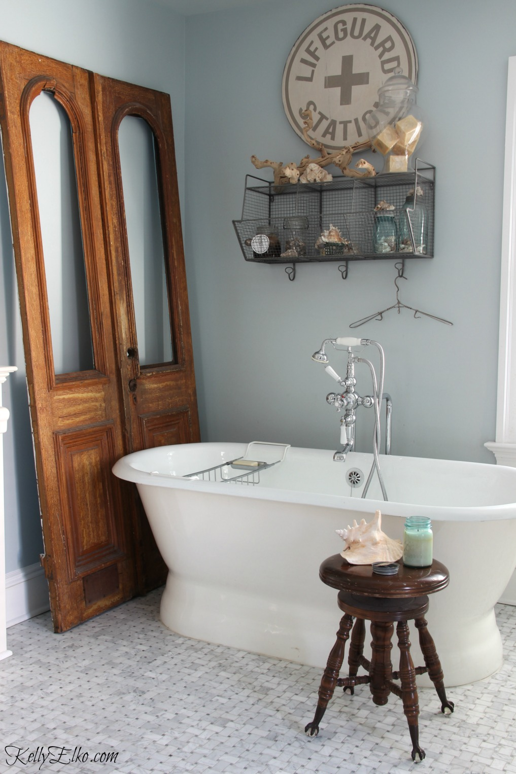 Master bathroom with free standing tub and antique wood doors that add warmth kellyelko.com