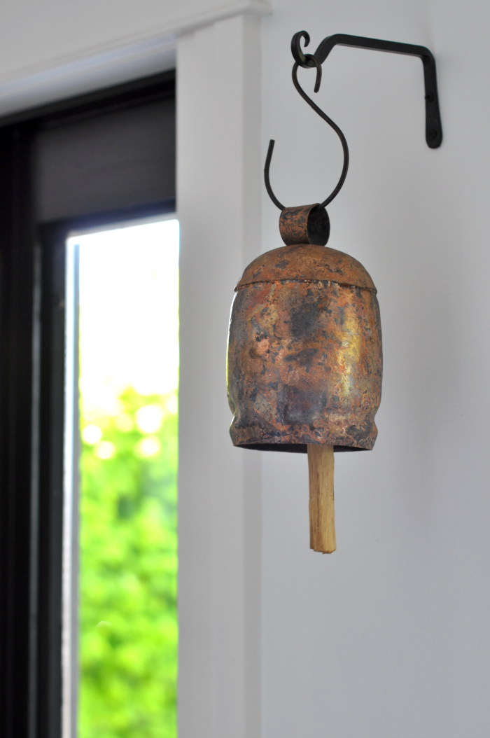 Copper bell hung from the wall is a fun accent to any home