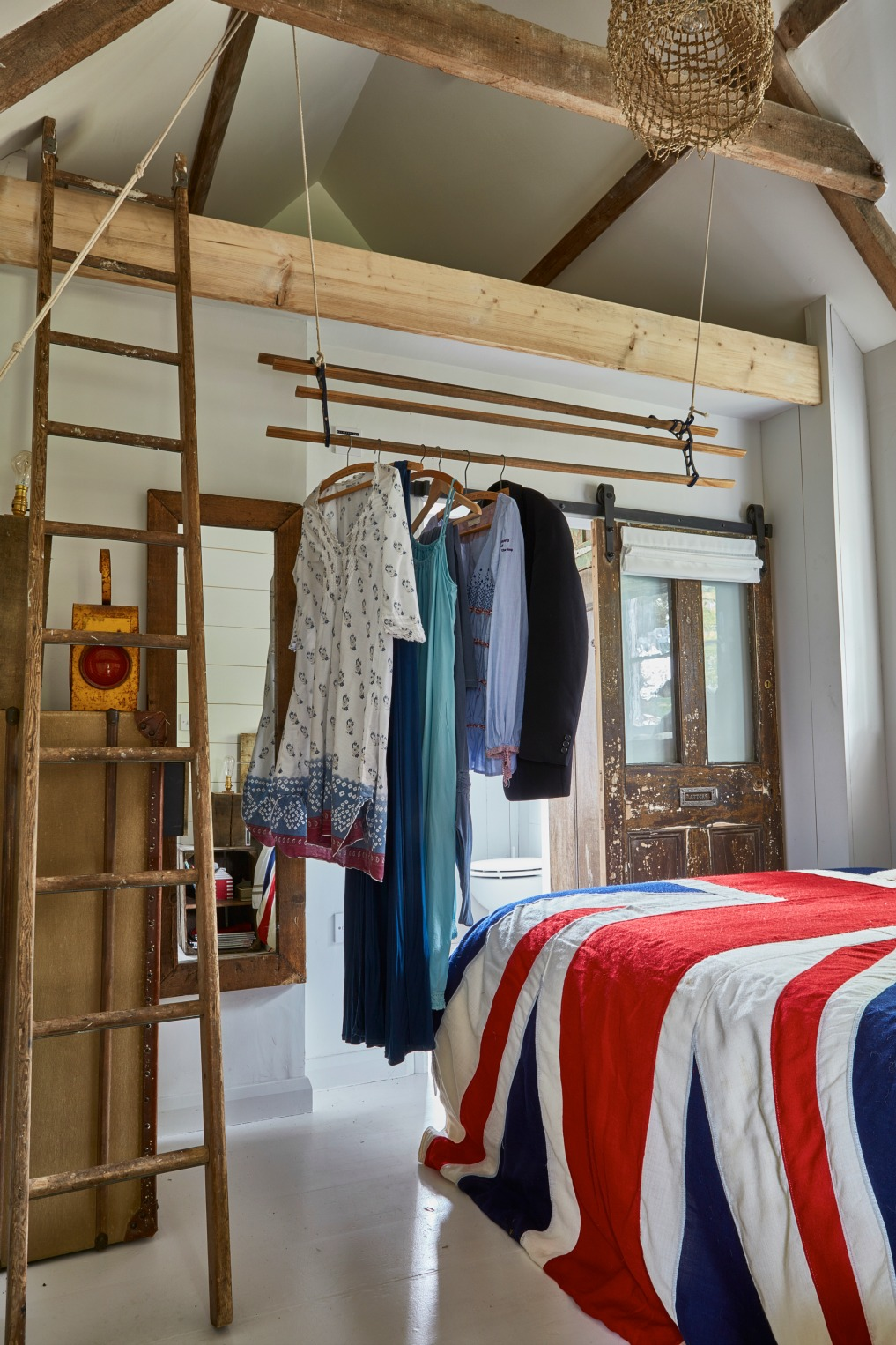 Cottage bedroom complete with old ceiling beams and a pulley system in place of a closet kellyelko.com