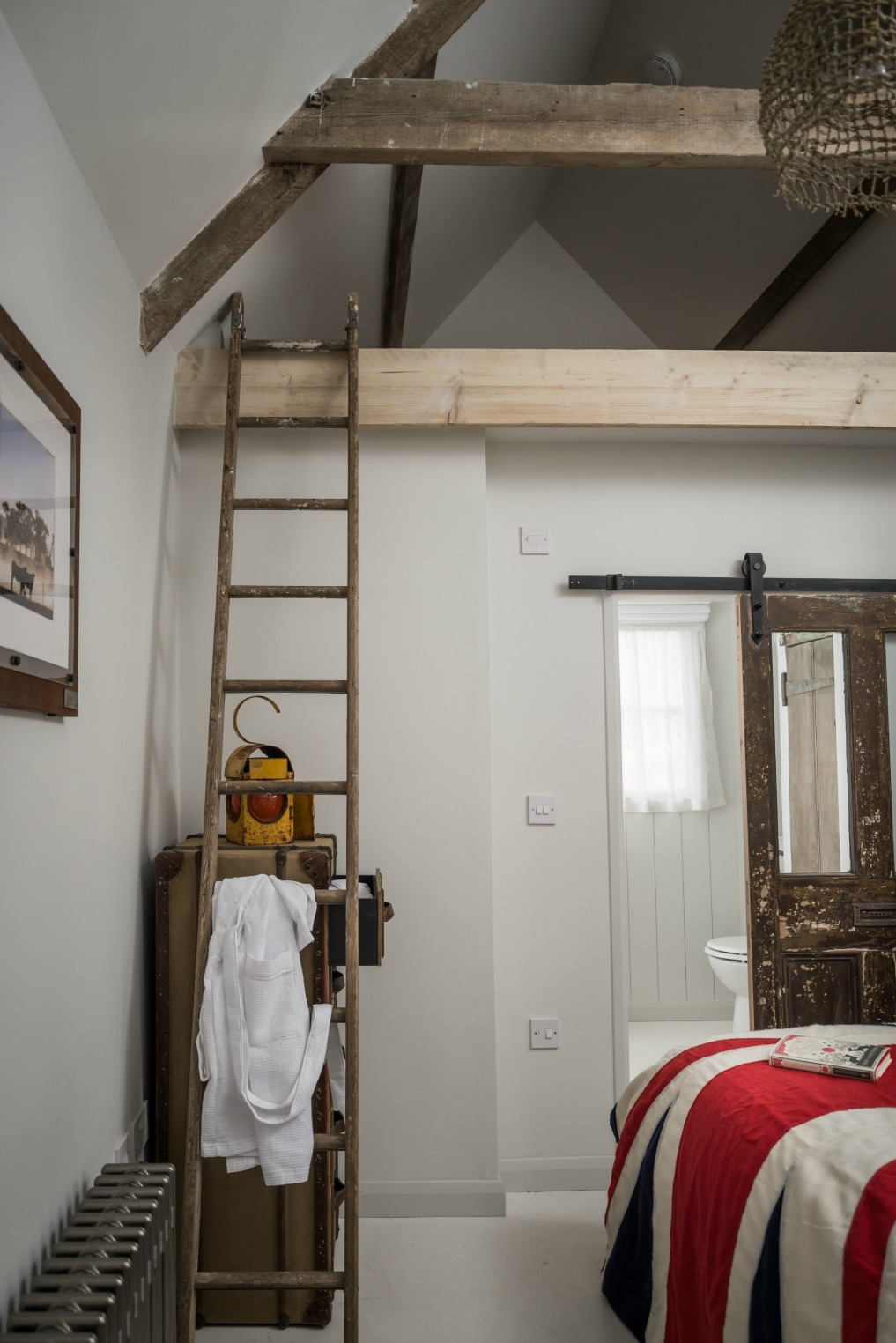 A vintage ladder leads to a loft in the bedroom kellyelko.com