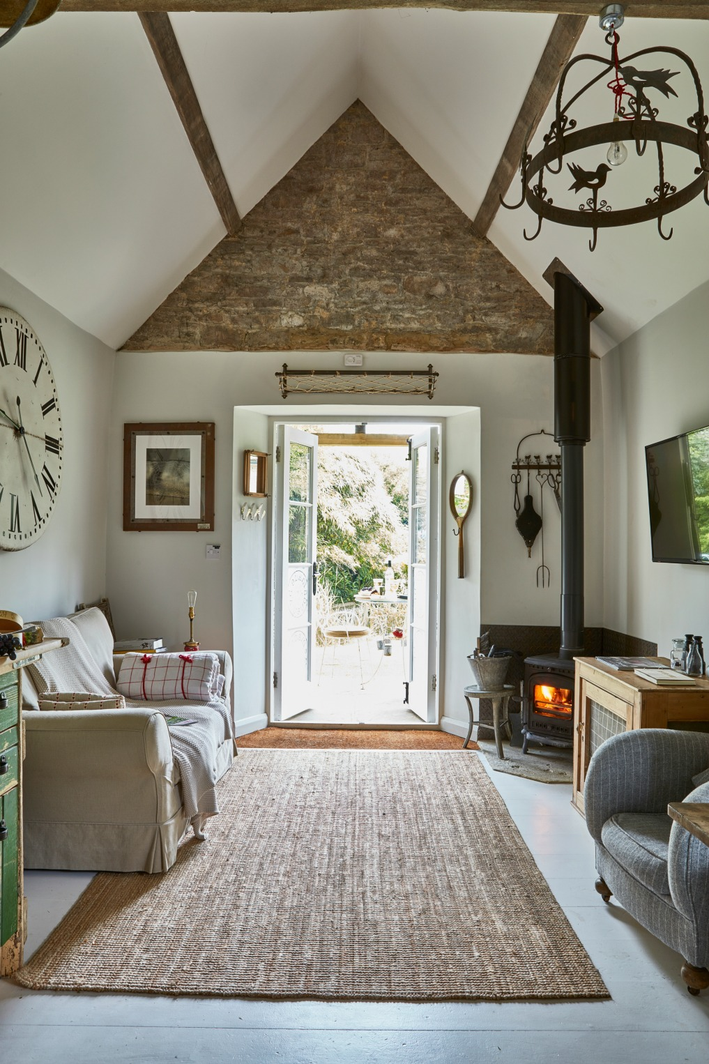 Tiny cottage family room - love the original stone walls and beams kellyelko.com