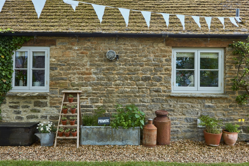 Stone cottage with unique planters kellyelko.com