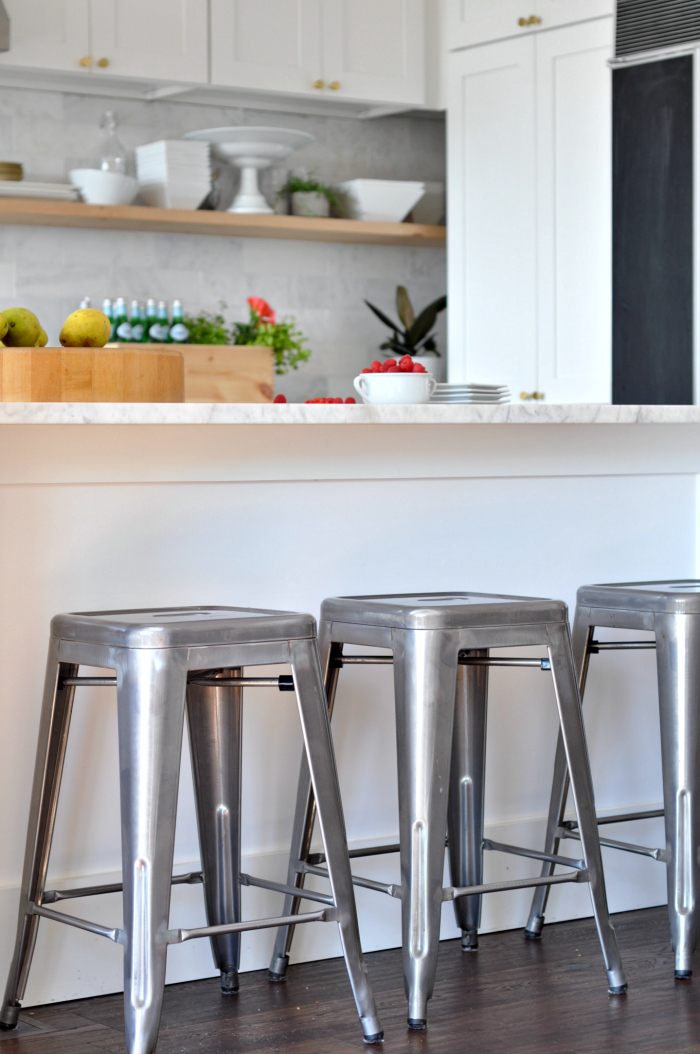 Galvanized counter stools in a white kitchen