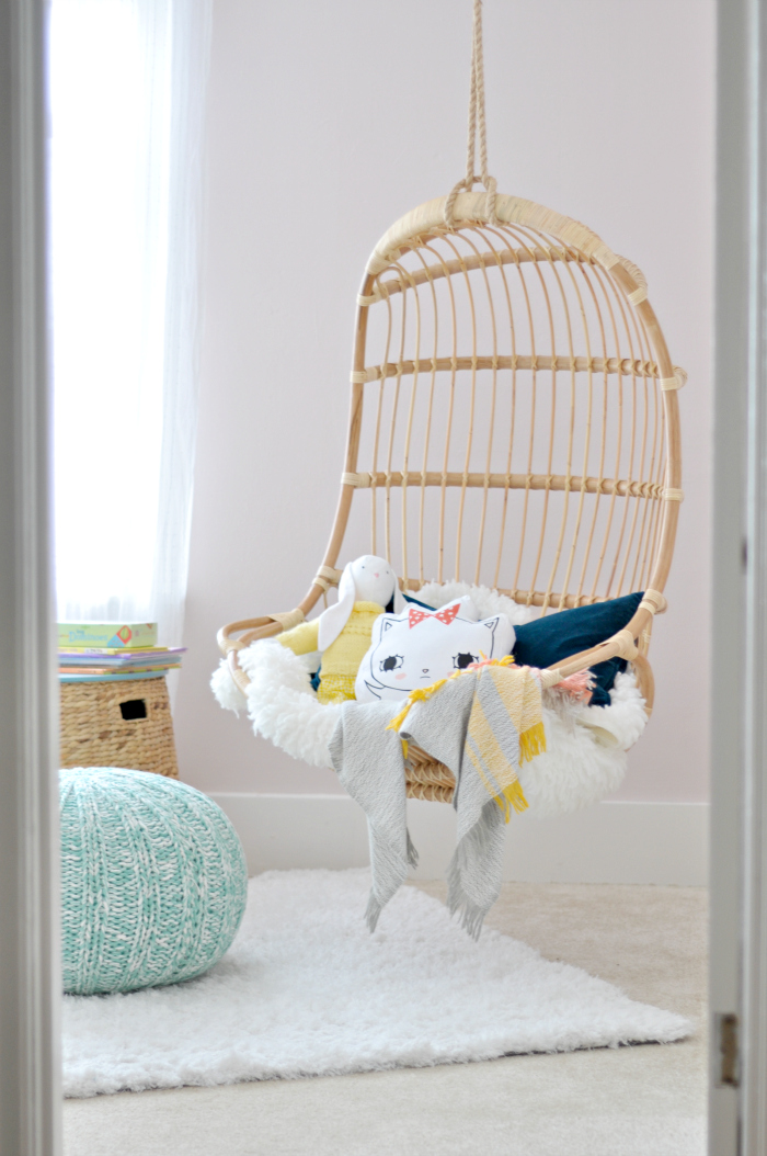 Rattan swing in a little girls bedroom