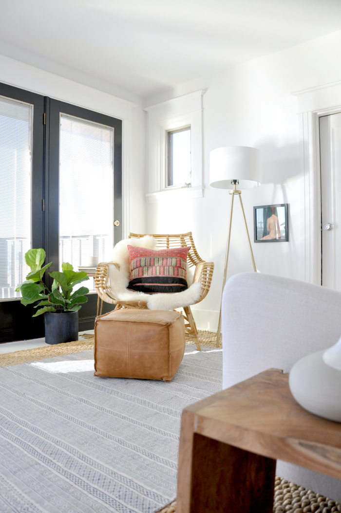 Cozy reading nook in the bedroom - love the rattan chair and leather pouf