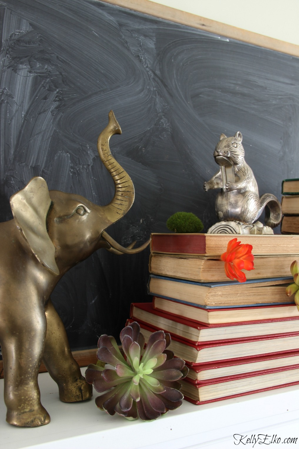 Vintage brass animals, books and a chalkboard combine in one stunning winter mantel kellyelko.com