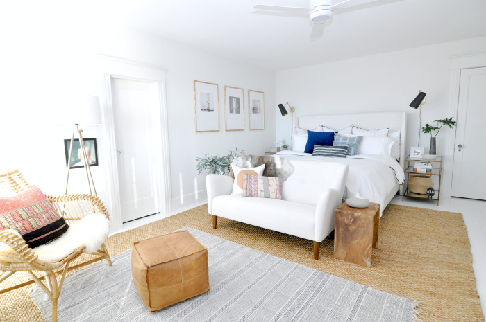 White master bedroom with texture from jute rug, leather pouf, rattan chair and wood accents