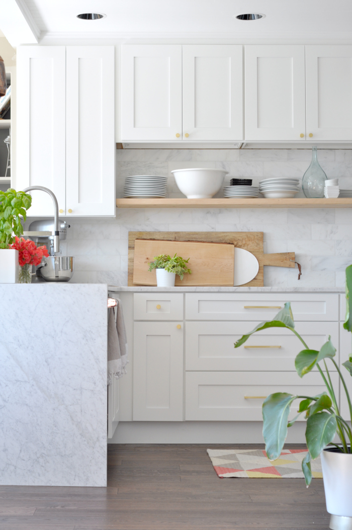 Beautiful white kitchen with marble and floating wood shelves