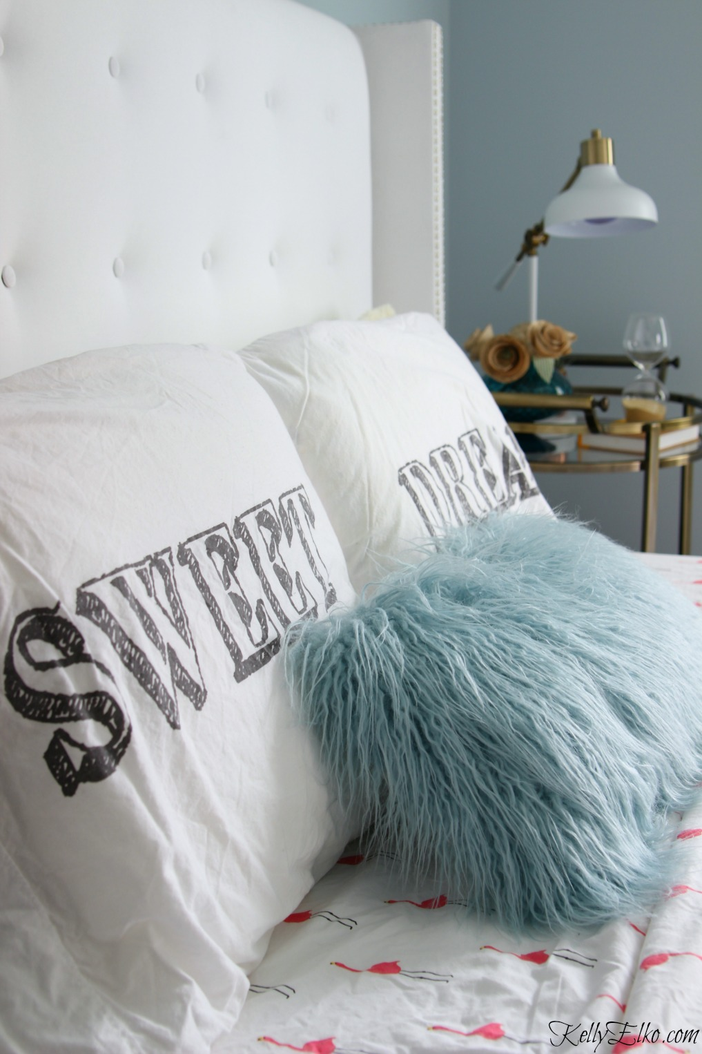 Love this glam tufted white headboard and fun mix of pillows and bedding kellyelko.com