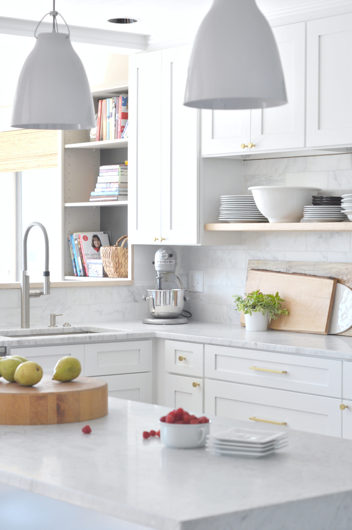 White marble kitchen with wood floating shelves and brass cabinet pulls